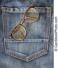 blue jeans pocket closeup with eyeglasses