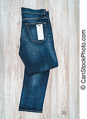 Blue jeans with price tag on wooden background .