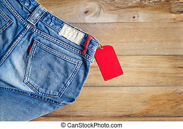 Blue jeans with red blank tag on wooden background