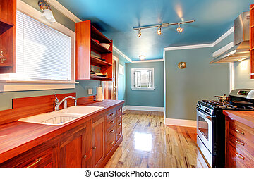 Blue kitchen with cherry cabinets and shiny floor.