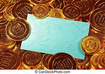 Blue kraft paper postcard in gold coins heap