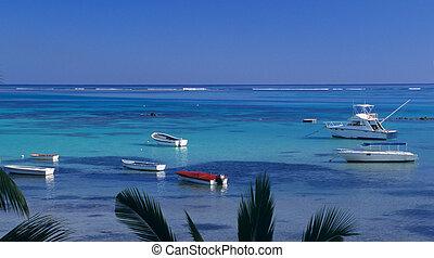 Blue lagoon at Bain Beauf beach with boats. Cape Malheureux,...