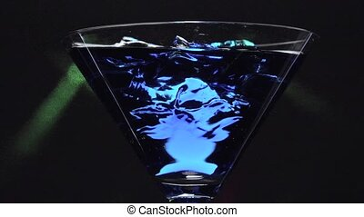 Blue lagoon over ice cubes - closeup with black background...