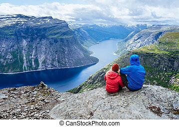 Blue lake in Norway near Trolltunga - Couple sits on rock...