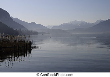 Blue lake of annecy and mountains on winter morning