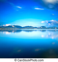 Blue lake sunset and sky reflection on water. Versilia...