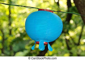 Blue lantern on Buddha's birthday on a blurry floral green background