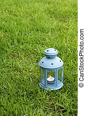 Blue Lantern, with burning candle inside, on green grass