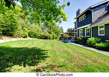 Blue large house with backyard and green landscape.