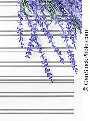 Blue lavender flowers on empty sheet music paper