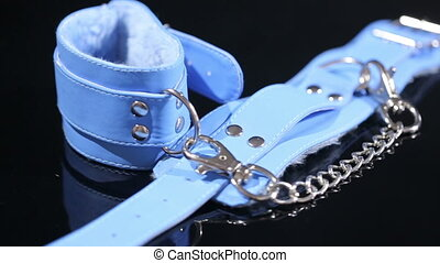 blue leather handcuffs in black background. sex toy