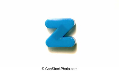 Blue letter z lifting off white background in slow motion