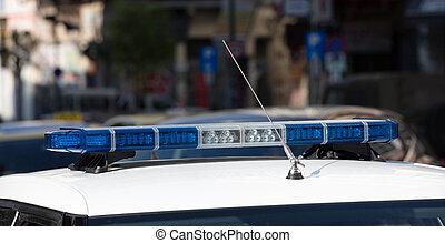 Blue light flasher at police car top, defocused city street background