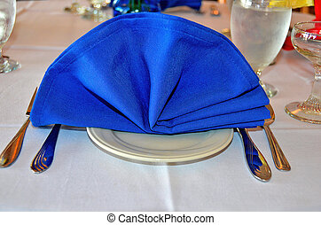 blue linen napkin - Fanned out blue dinner napkin on table.