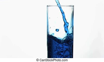 Blue liquid in super slow motion overflowing in a glass near...