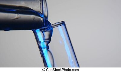 Blue liquid is poured from one tube into another in a modern medical laboratory