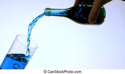 Blue liquid pouring into glass low