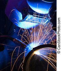 Blue lit MIG welder close - MIG welder uses torch to make ...