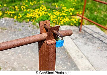Blue lock on old rusty car ramp, with blurred yellow ...