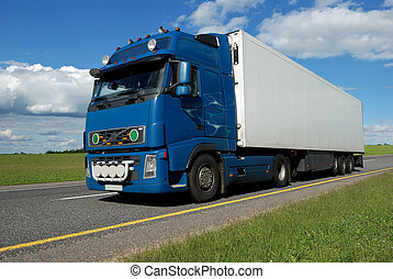 blue lorry with white trailer on the highway over blue cloudy sky