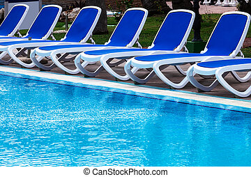 blue lounge chairs by the pool