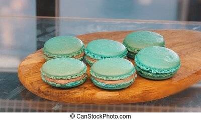 Blue macaroons on a wooden plank behind the shop window....