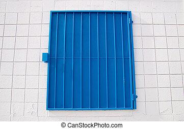 Blue mesh shutter on white wall