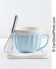 Blue mixing bowl with wisp for baking on white background