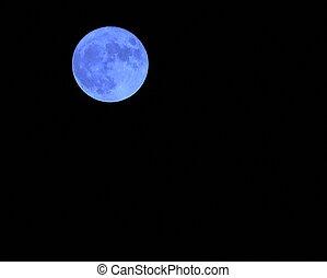 Blue moon in the dark sky on a night