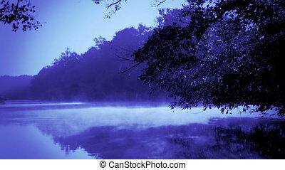 Blue morning fog on a calm river