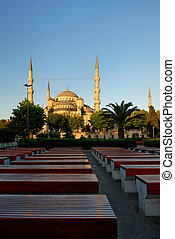 Blue Mosque at sunrise, perspective rows of benches in foreground