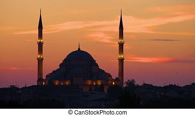 Blue Mosque with lights and a colourful sky at sunset