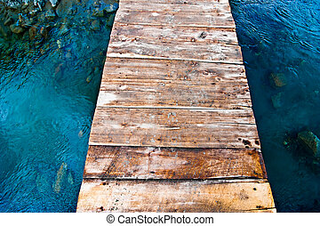 Blue mountain river with wooden bridge