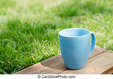 Blue mug on wooden board with green grass space.