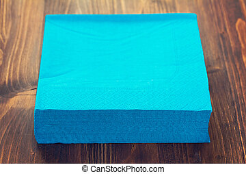 blue napkin on brown wooden background