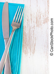 blue napkin on white background with fork and knife