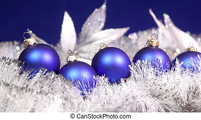Blue New Year's balls and tinsel on a blue background.