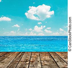 Blue ocean and sky above wooden floor