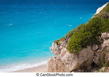 Blue ocean and white rocks and sand