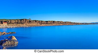 Blue ocean, rocks, pine forest, clear sky, beach on sunset...