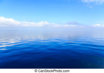 Blue ocean water with clouds in the background