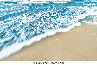 Blue ocean waves background with golden sand.