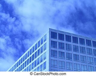 Office windows in front of partially cloudy sky. Tinted blue. Plenty of room for text.