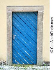 Blue old door in a building wall