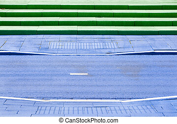 Blue painted bicycle path and green steps