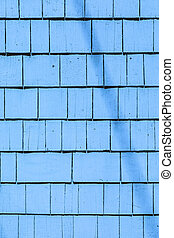 blue painted wooden shingles at the roof