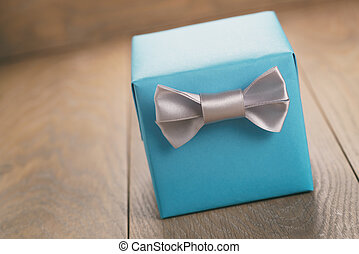blue paper gift box with silver ribbon bow on oak table