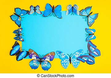 Blue paper in center with blue butterfly on yellow background with copy space
