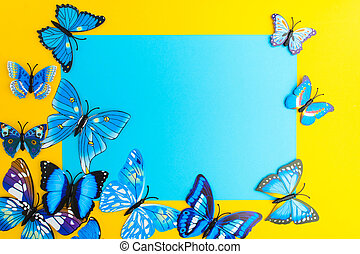 Blue paper with butterfly decoration on yellow background with copy space