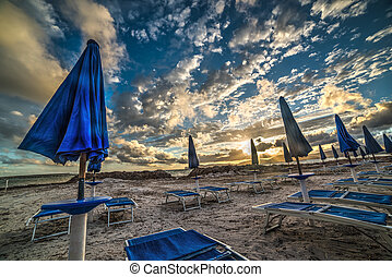 blue parasols and beach chairs under a dramatic sky